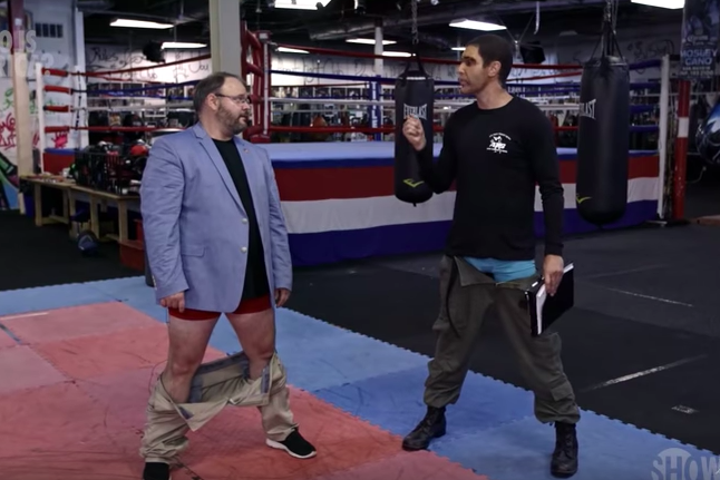 Rep. Jason Spencer stands in a gym with his pants around his ankles, talking to Baron Cohen in disguise.