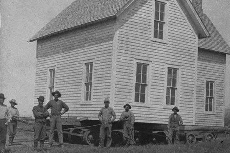 Several man stand beside a two-story house on a large cart.