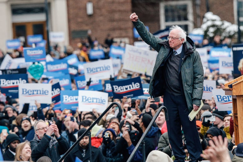 Bernie Sanders raising a fist of solidarity surrounded by campaign supporters.