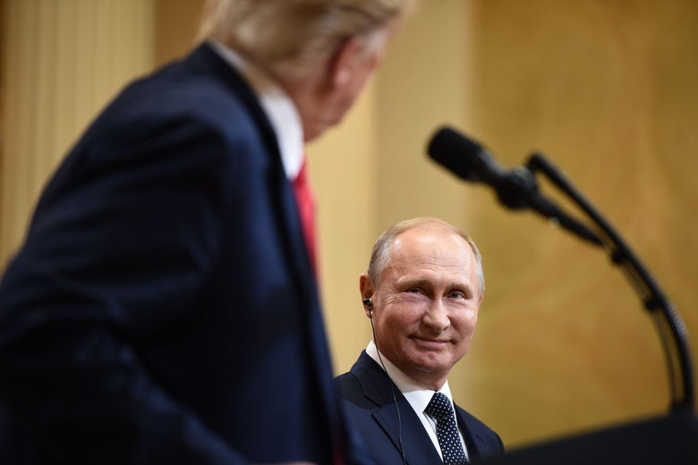 Putin smiles as Trump looks on.