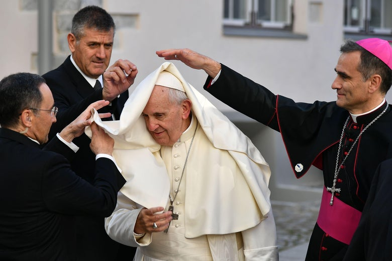 Three people stand around Pope Francis and reach out to pull down his cape, which has blown onto his head.