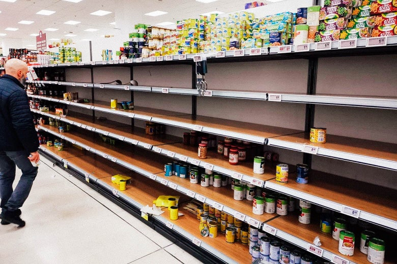 A man stares at an empty canned goods aisle in the grocery store, with just a few choices left.