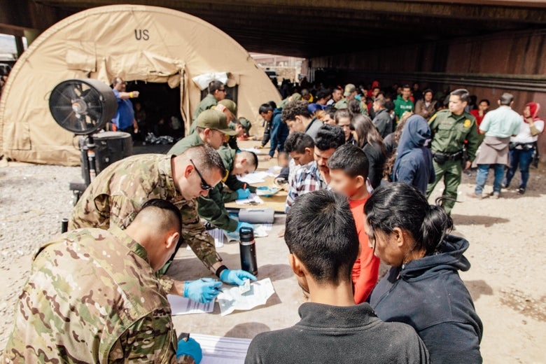 U.S. Border Patrol agents, including members of U.S. Border Patrol's BORSTAR teams (in tactical uniforms) provide food, water, and medical screening to migrants at a processing center in El Paso, Texas on March 22.