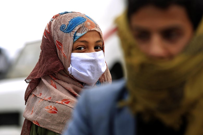 A woman wearing a colorful patterned hijab and face mask looks at a man.