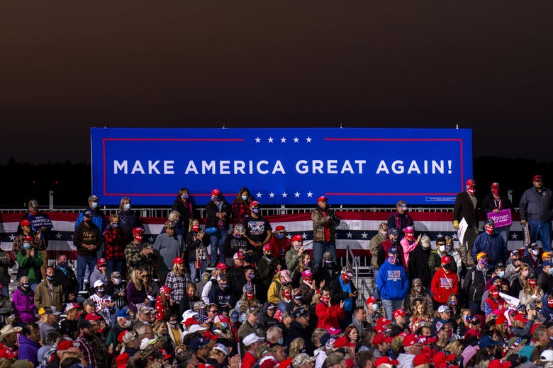 "Rows of people, many wearing red caps, sit or stand below a long ""Make America Great Again!"" sign."
