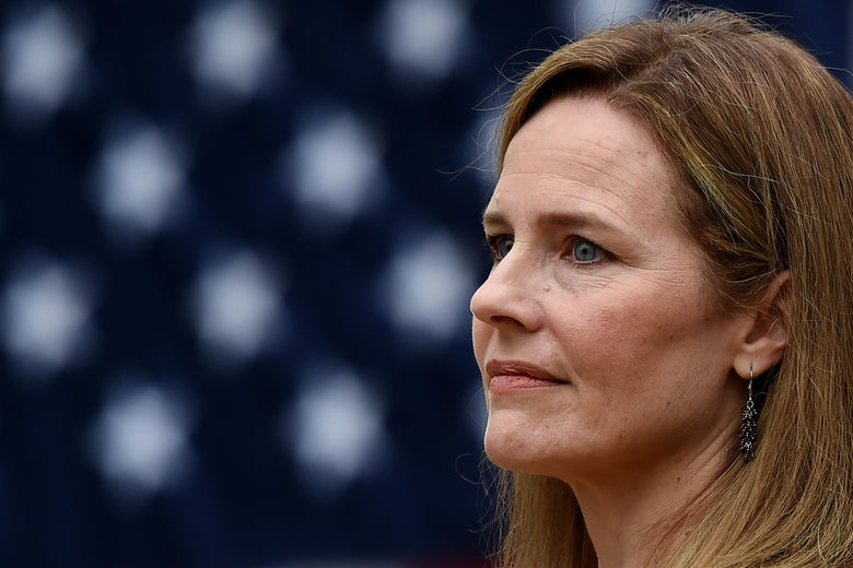 Amy Coney Barrett in profile with an American flag behind her.