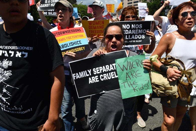 Protesters march and carry signs decrying the Trump administration's family separation policy.