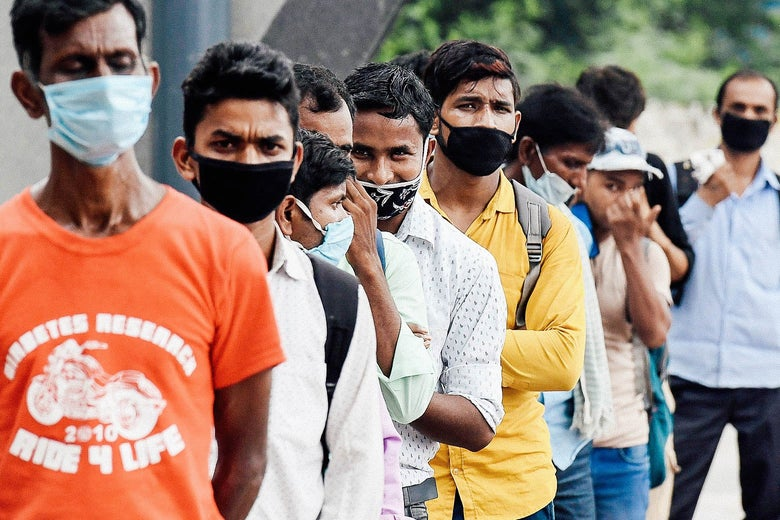 Men wearing masks stand in a queue.