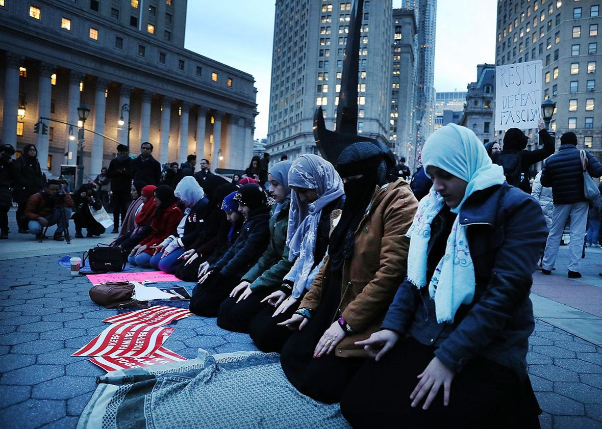 Muslim women pray before a protest in lower Manhattan against the polices of President Donald Trump on February 1, 2017 in New York City.