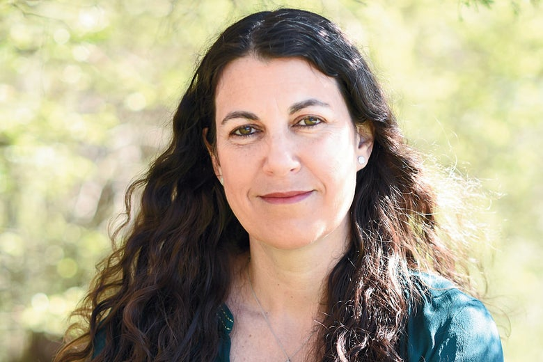 A white woman with long dark hair and an open-necked shirt.