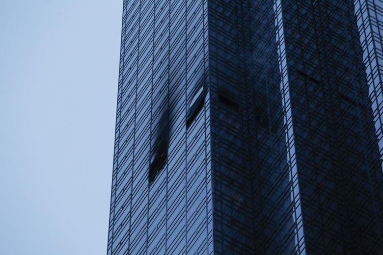 On the side of Trump Tower, two windows are burnt and broken.