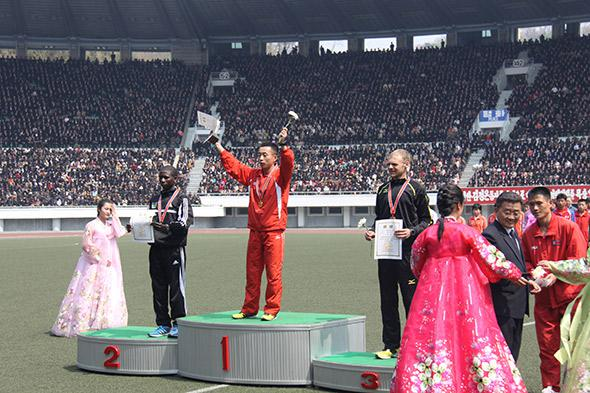 The winner celebrates his victory inside Kim Il-Sung Stadium. The men's race was won by a local Korean for the first time in several years.