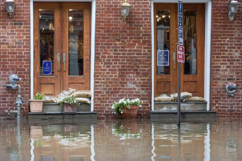 Sandbags sit in doorways as flooding occurs outside buildings in Alexandria, Virginia.