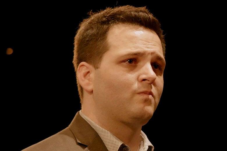 A close-up of a man's face in front of a black backdrop.