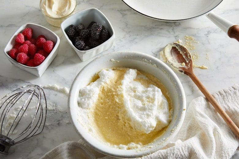 A white powder is partially mixed into batter in a bowl. Beside the bowl there are smaller bowls of blackberries and raspberries.