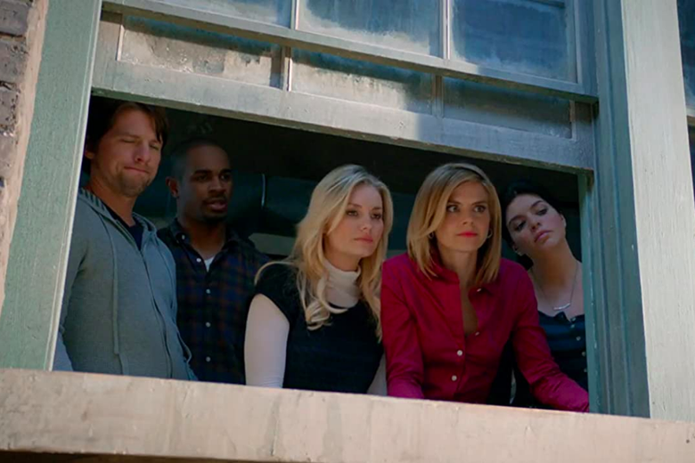 Elisha Cuthbert, Zachary Knighton, Damon Wayans Jr., Casey Wilson, and Eliza Coupe look through a window.