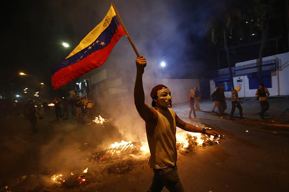 An opposition demonstrators holds a Venezuelan flag in front of a burning barricade during a protest against President Nicolas Maduro's government in Caracas.