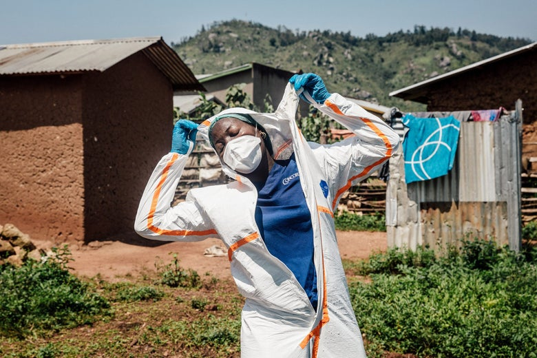 World Health Organization worker Belinda Landu changes her protective outfit.