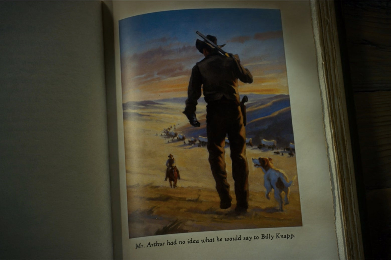 An illustration of a cowboy cresting a hill and walking away from the viewer toward a distant wagon train.