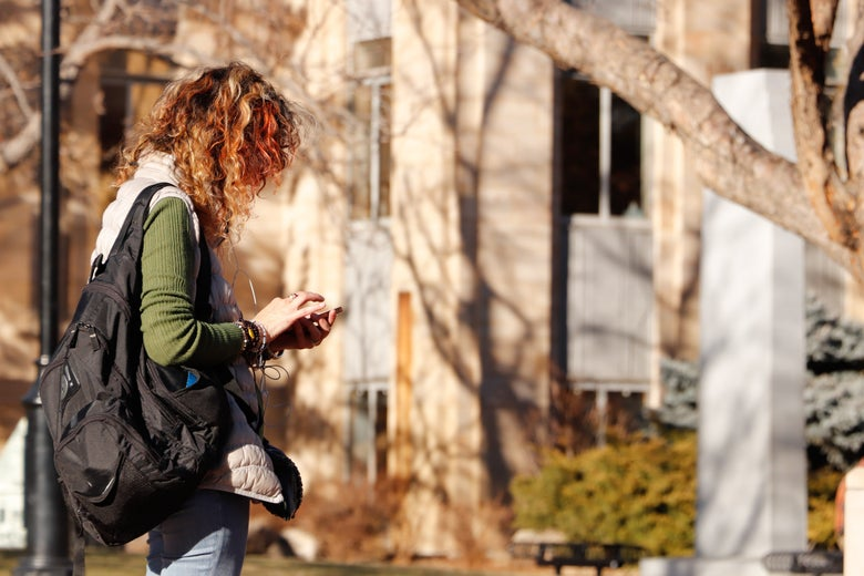 A woman standing outside, looking at her phone.