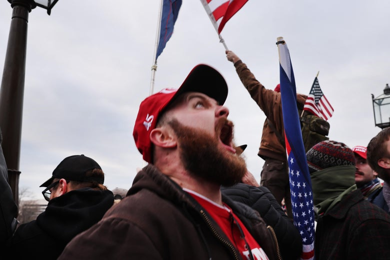 A white man wearing a red 45 hat screams skyward, standing in a crowd of other male Trump supporters, some waving American flags.