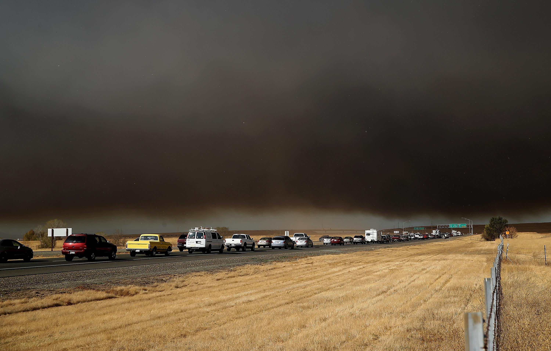 Cars stuck in traffic, with smoke overhead.