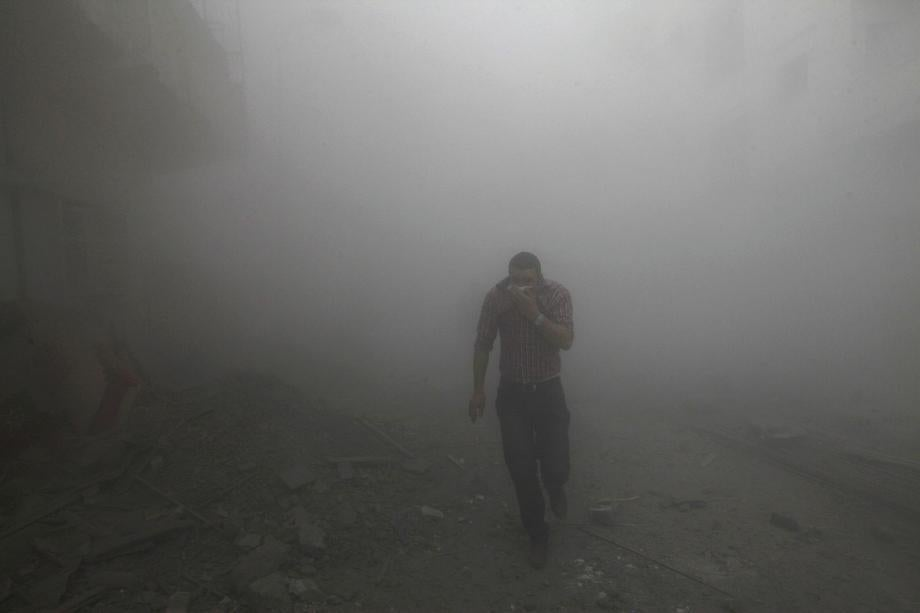 A man runs among rubble as smoke rises from buildings damaged by what activists said were missiles fired by a Syrian air force fighter jet loyal to President Bashar al-Assad in Raqqa province, eastern Syria on March 12, 2013.