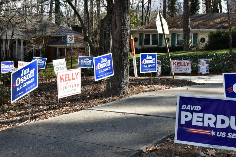 Signs for Jon Ossoff, Kelly Loeffler, and David Perdue line a street in Atlanta