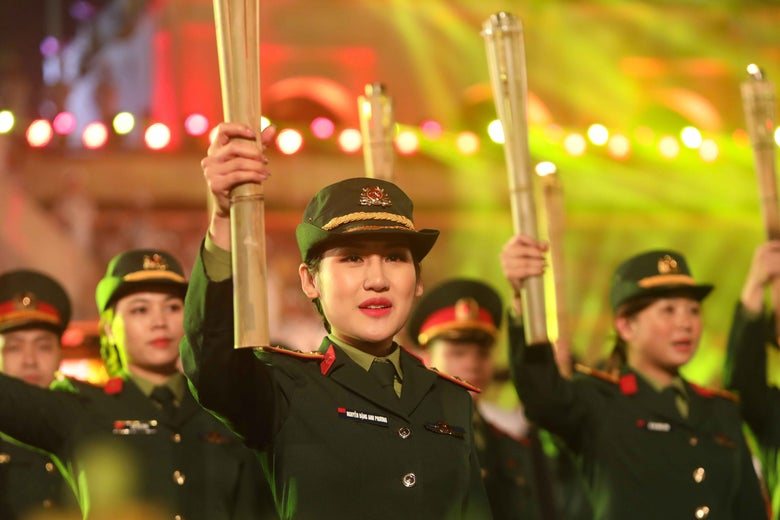 Women in uniform hold up torches.