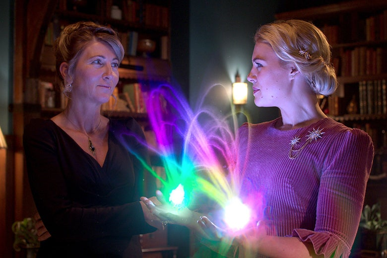 Alfea headmistress Farah Dowling stands next to a student, Stella, who holds shimmering arches of light in her hands, in a still from the TV show Fate: The Winx Saga.