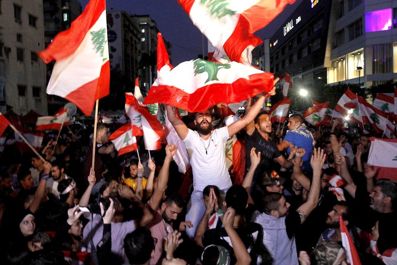 Lebanese protesters gather in Sidon on Monday. They are holding flags and chanting.