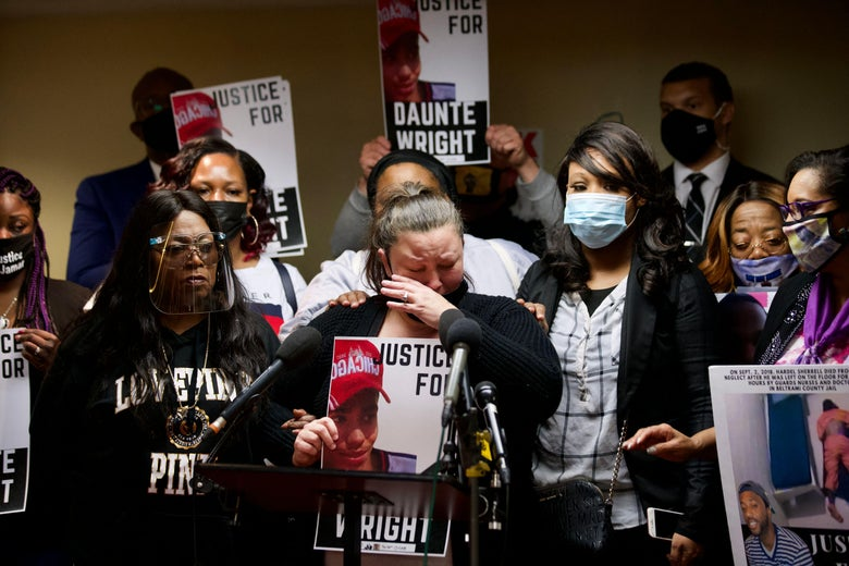"""Katie Wright cries as she stands at a mic surrounded by supporters. Several, including Katie, are holding posters that say """"Justice for Daunte Wright."""""""