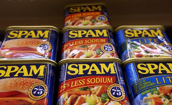 Cans of Spam are displayed on a shelf at Cal Mart grocery store.