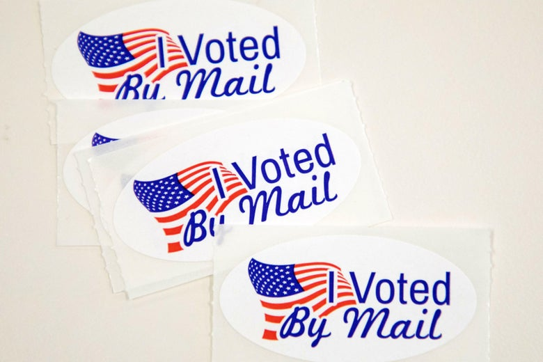 """Stickers that read """"I Voted By Mail"""" sit on a table waiting to be stuffed into envelopes by absentee ballot election workers at the Mecklenburg County Board of Elections office in Charlotte, NC on September 4, 2020."""