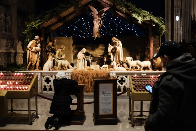 A person kneels in front of a Nativity scene at St. Patrick's Cathedral in New York. Behind her a person wearing a mask stands looking at their phone.