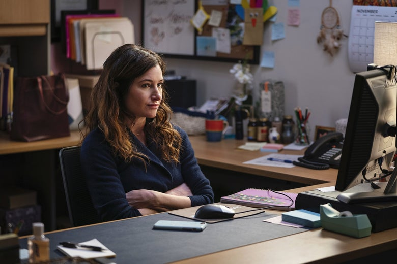 Kathryn Hahn crosses her arms over her chest while sitting at a desk.