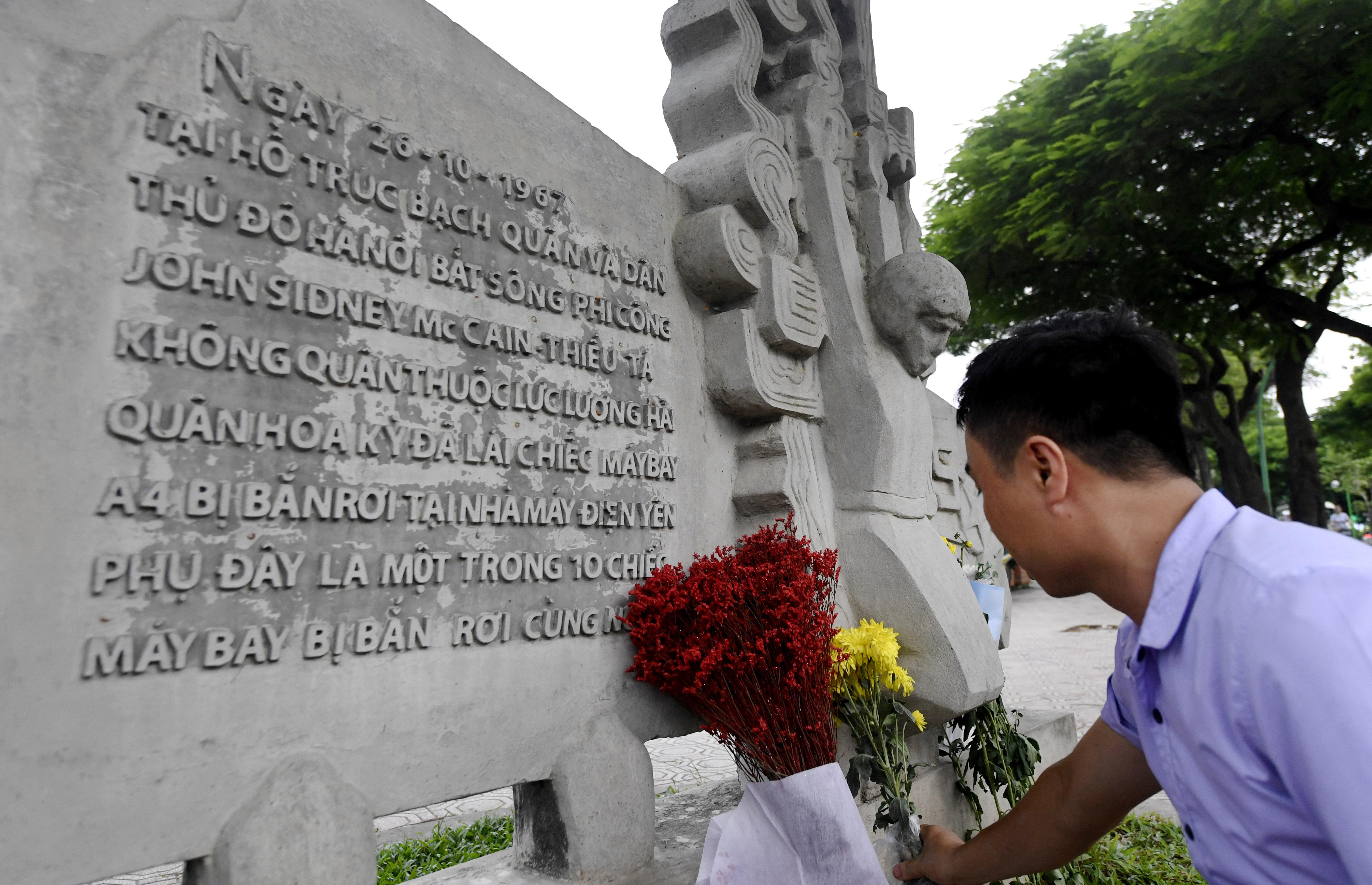 A Vietnamese man places flowers for McCain at a sculpture depicting his capture in Vietnam.