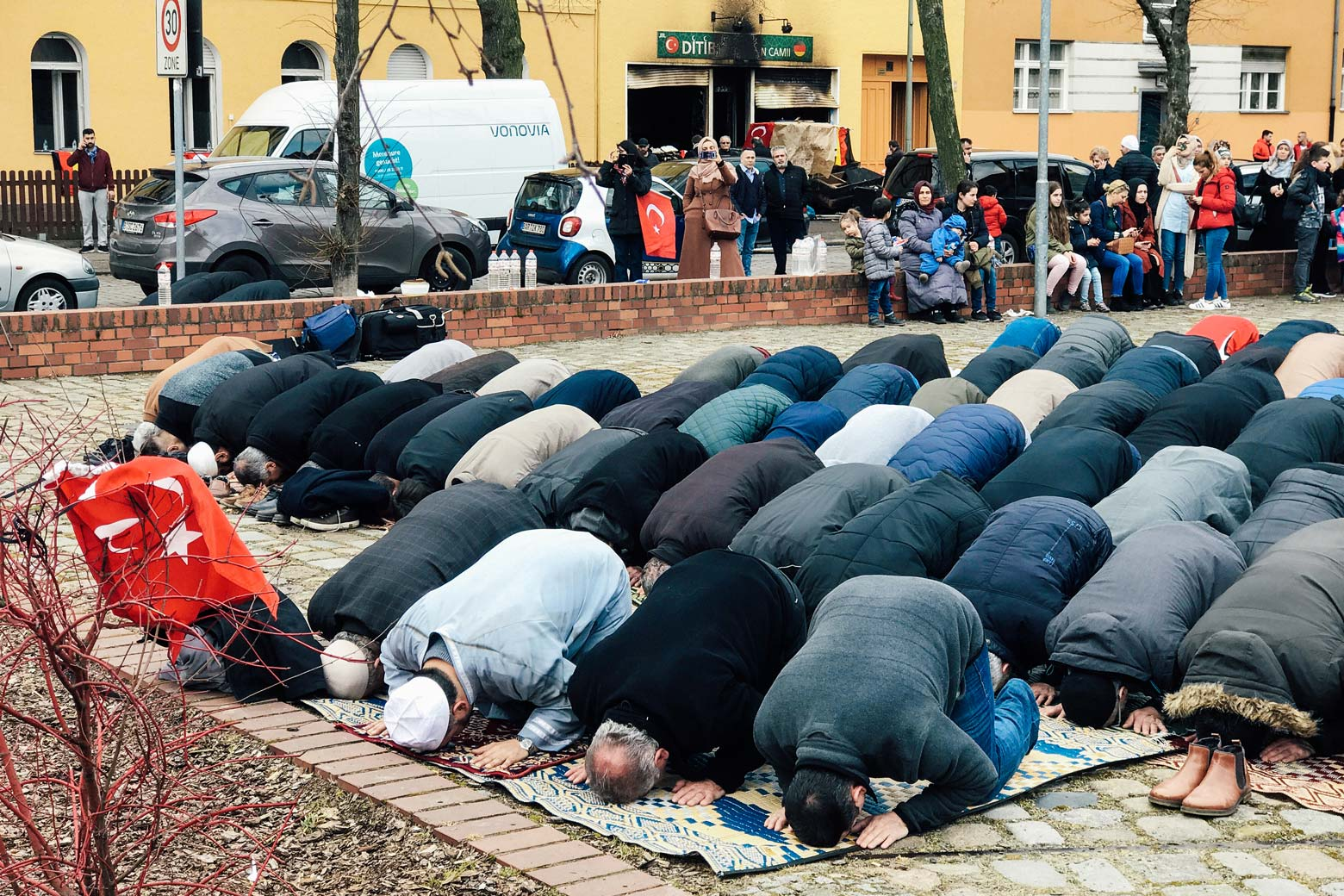 People pray near a mosque after it was destroyed by a fire in Berlin on March 11.