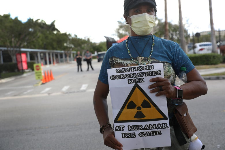 "A woman in a blue t-shirt and face mask stares at the camera, holding a sign that reads, ""CAUTION!! CORONAVIRUS RISK AT MIRAMAR ICE CAGE."""