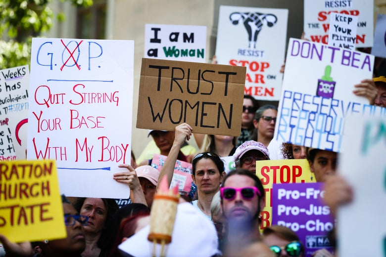 Women hold signs during a protest against recently passed abortion ban bills at the Georgia State Capitol building, on May 21, 2019 in Atlanta, Georgia.
