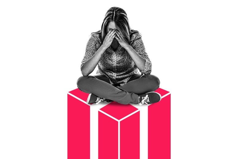 A woman sits with her hands over her face on top of an illustrated present.