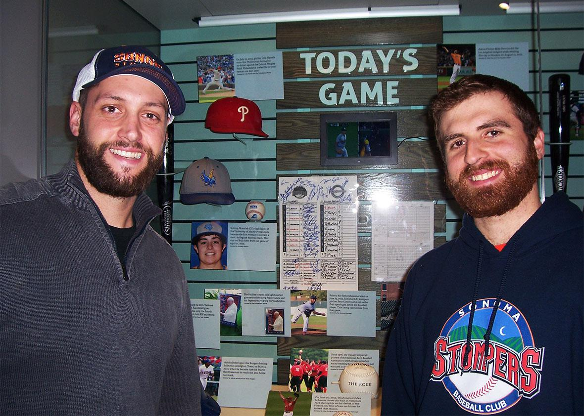 Sean Conroy and Isaac Wenrich pose in Cooperstown in front of a Hall of Fame display case containing the scorecard from the Stompers' Pride Night game.