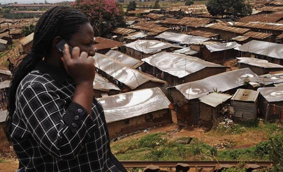 A woman speaks on a mobile phone in front of Kibera