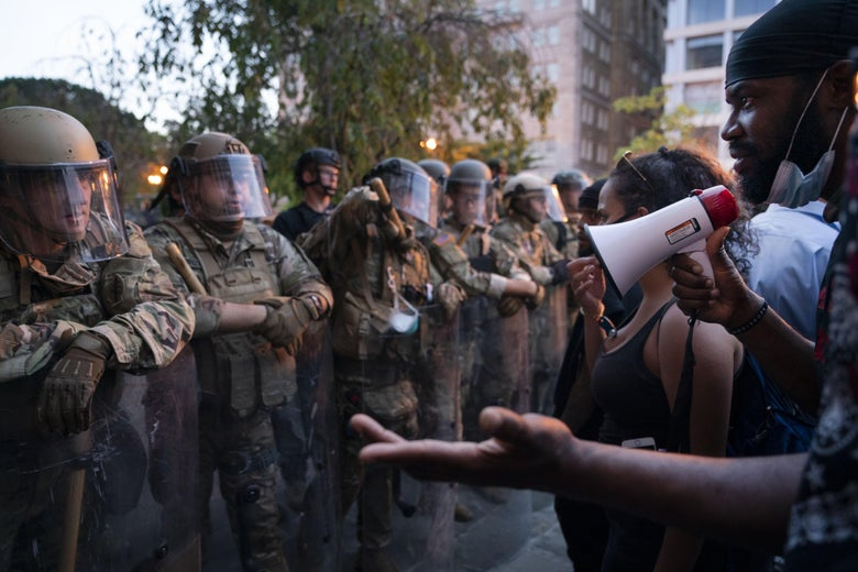 A protester with a bullhorn talks with a line of armed militarized police in camo and riot gear.