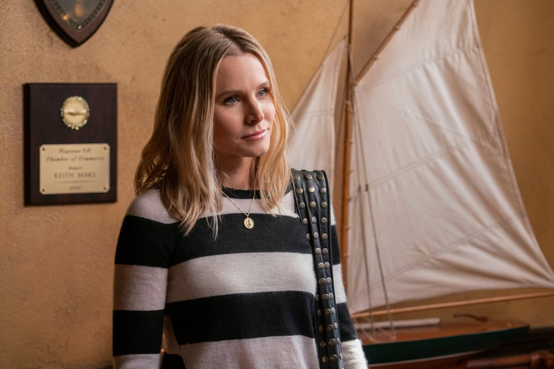 Kristen Bell stands in front of a large model ship.