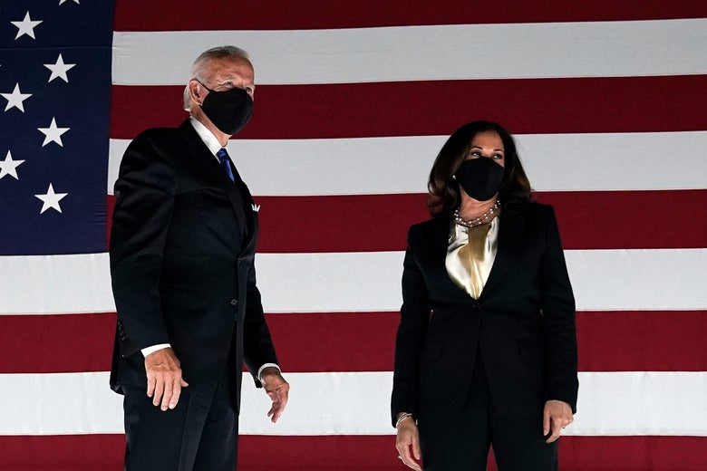 Joe Biden and Kamala Harris wear masks while standing in front of a giant U.S. flag.