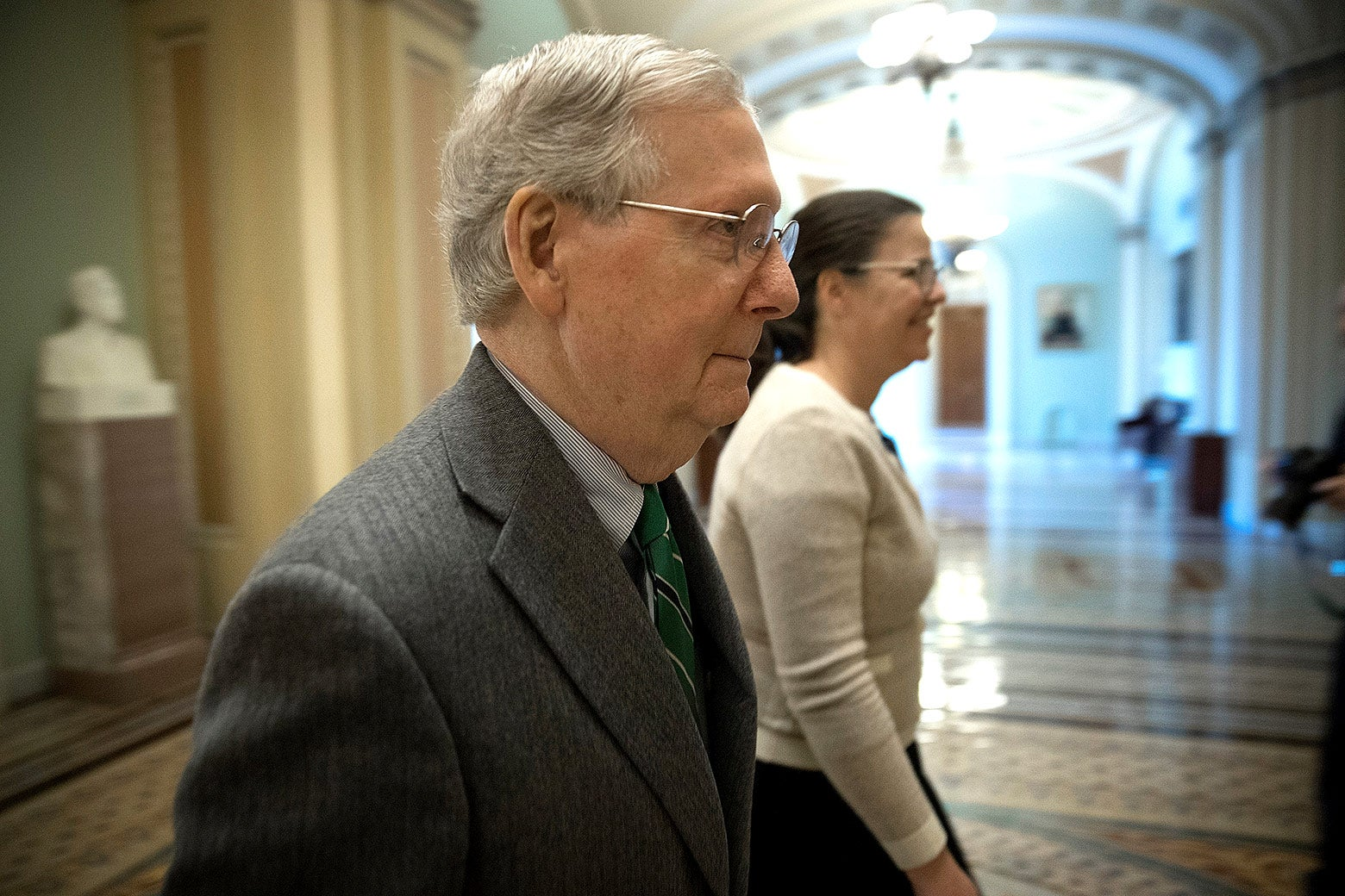 Mitch McConnell and an unidentified woman walk through the Capitol.