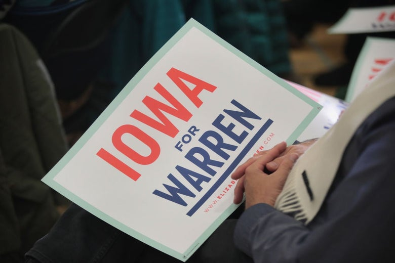 """An """"Iowa for Warren"""" sign in a rally attendee's lap."""