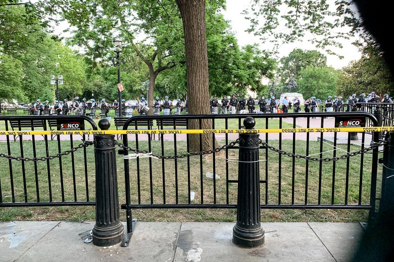 A line of officers and guardsman stand in the middle of the park, which is blocked off by fences and yellow tape.
