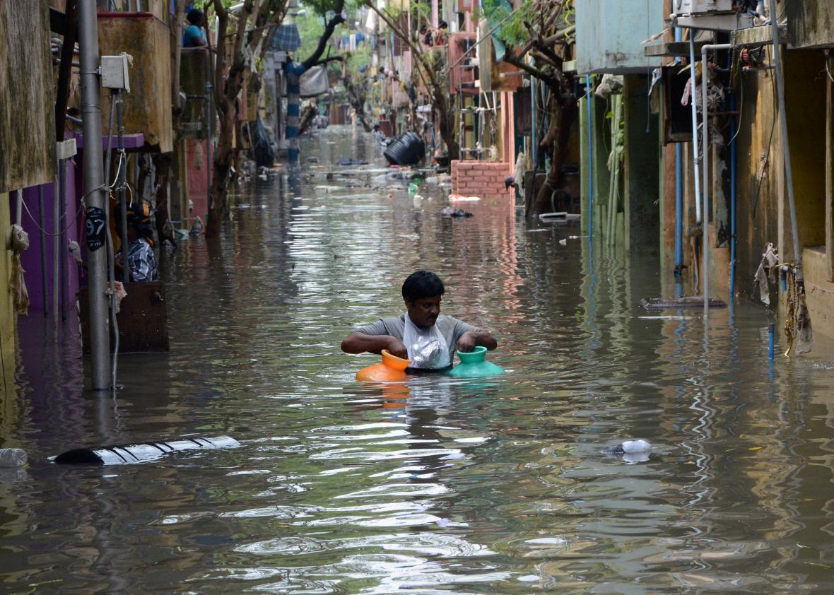 Indian residents stand in floodwater outside their homes following heavy rain in Alwal on the outskirts of Hyderabad on September 23, 2016.